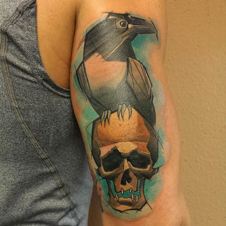 raven holding skull tattoo