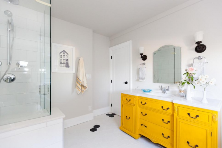 minimalist bathroom with bright yellow cabinet
