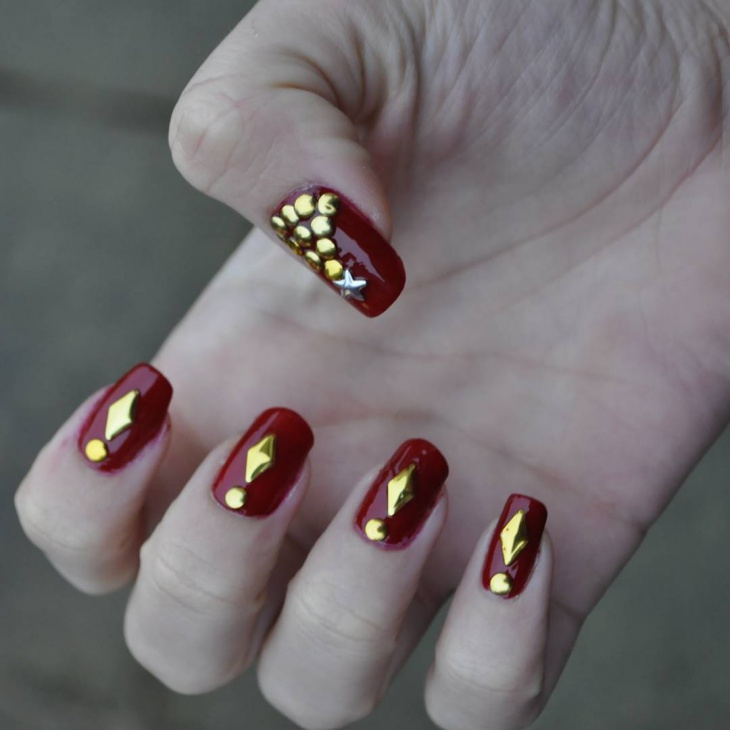 dark red and gold nail design