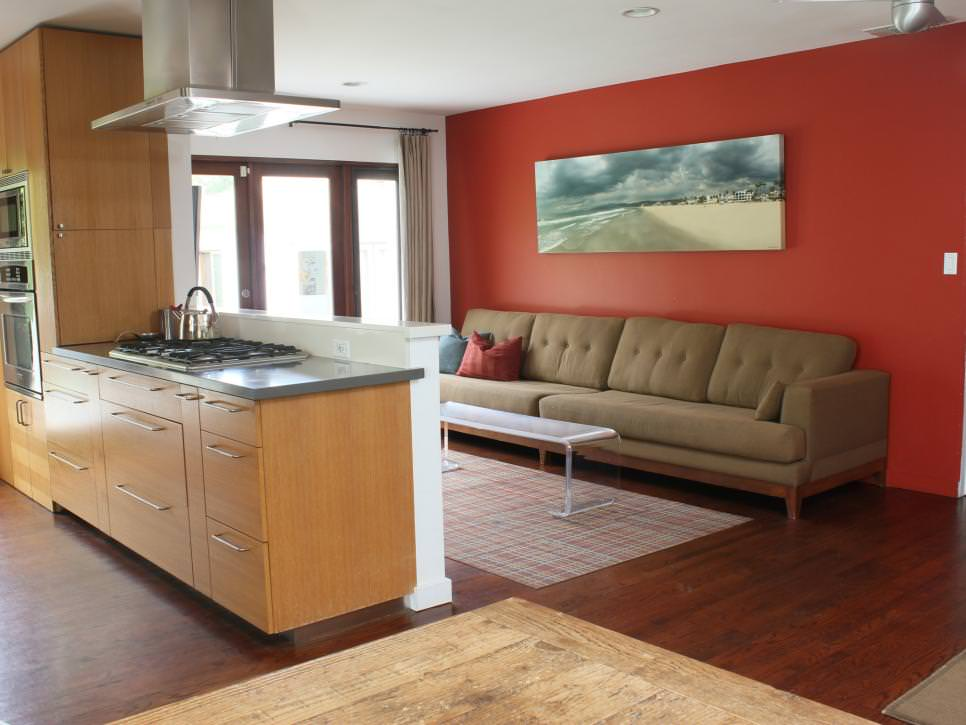 Red Modern Living Room And Connected Kitchen With Long Brown Sofa
