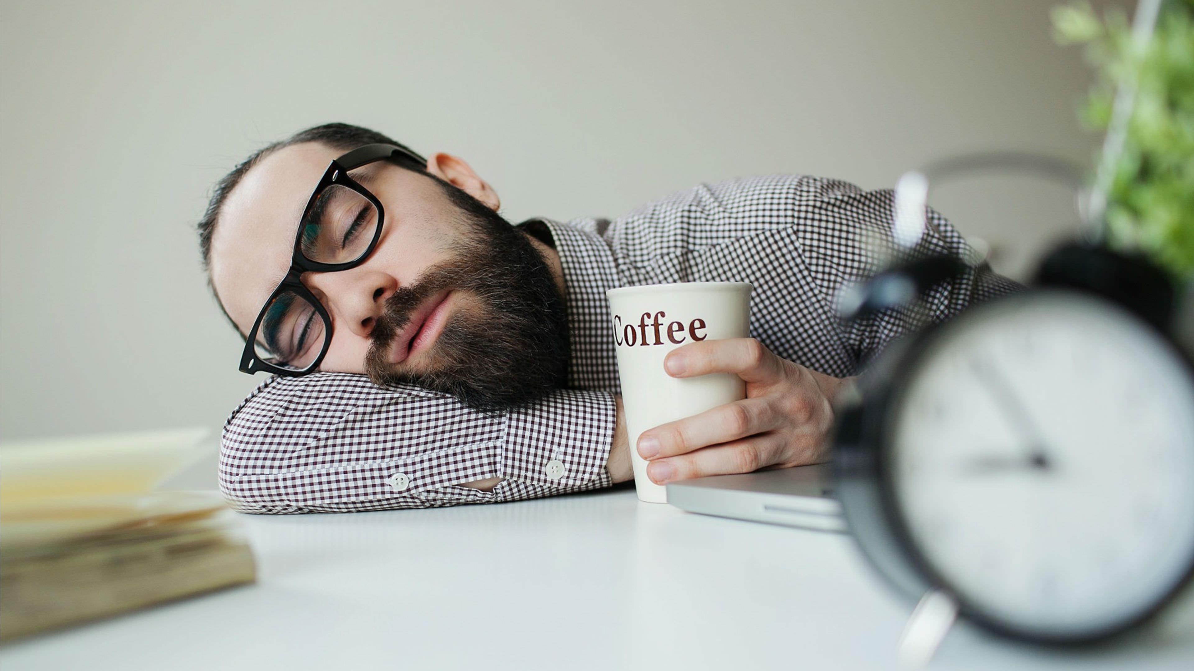 sleeping man with coffee cup