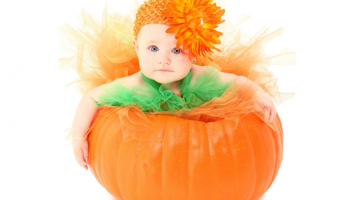 baby girl sitting in pumpkin