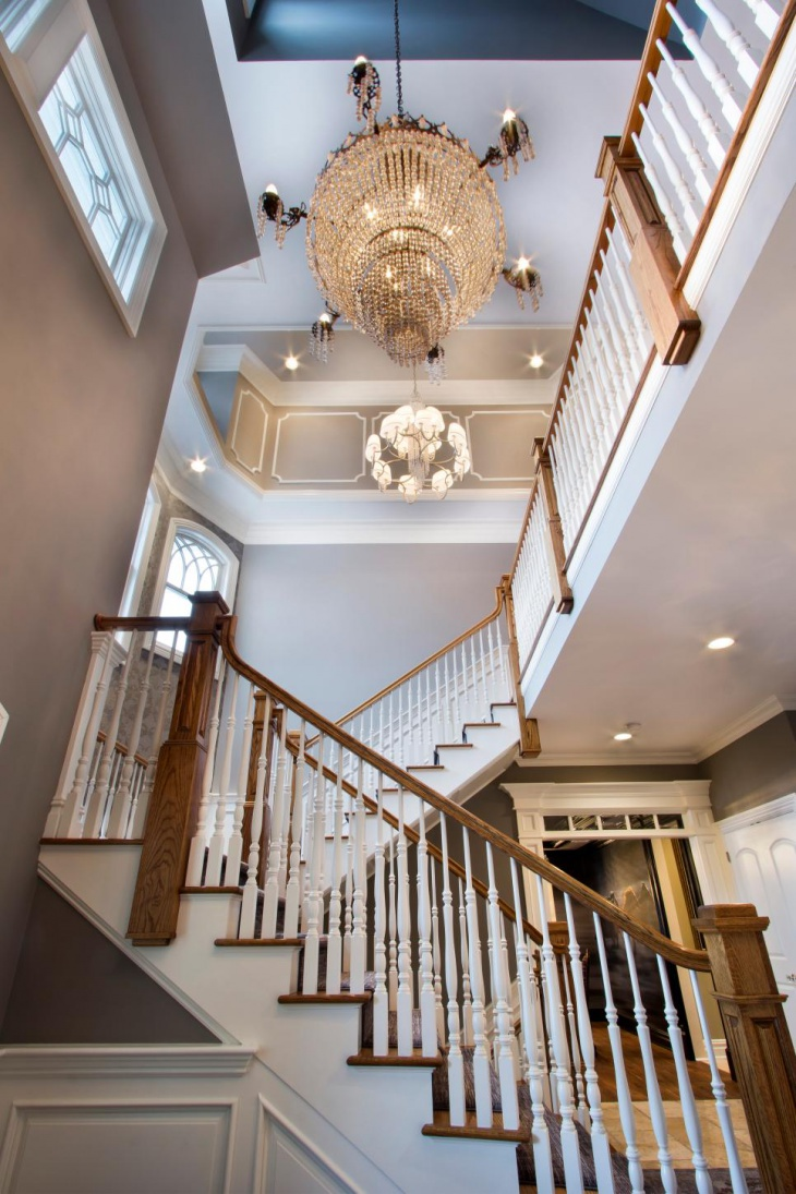 foyer crystal chandelier over turning staircase