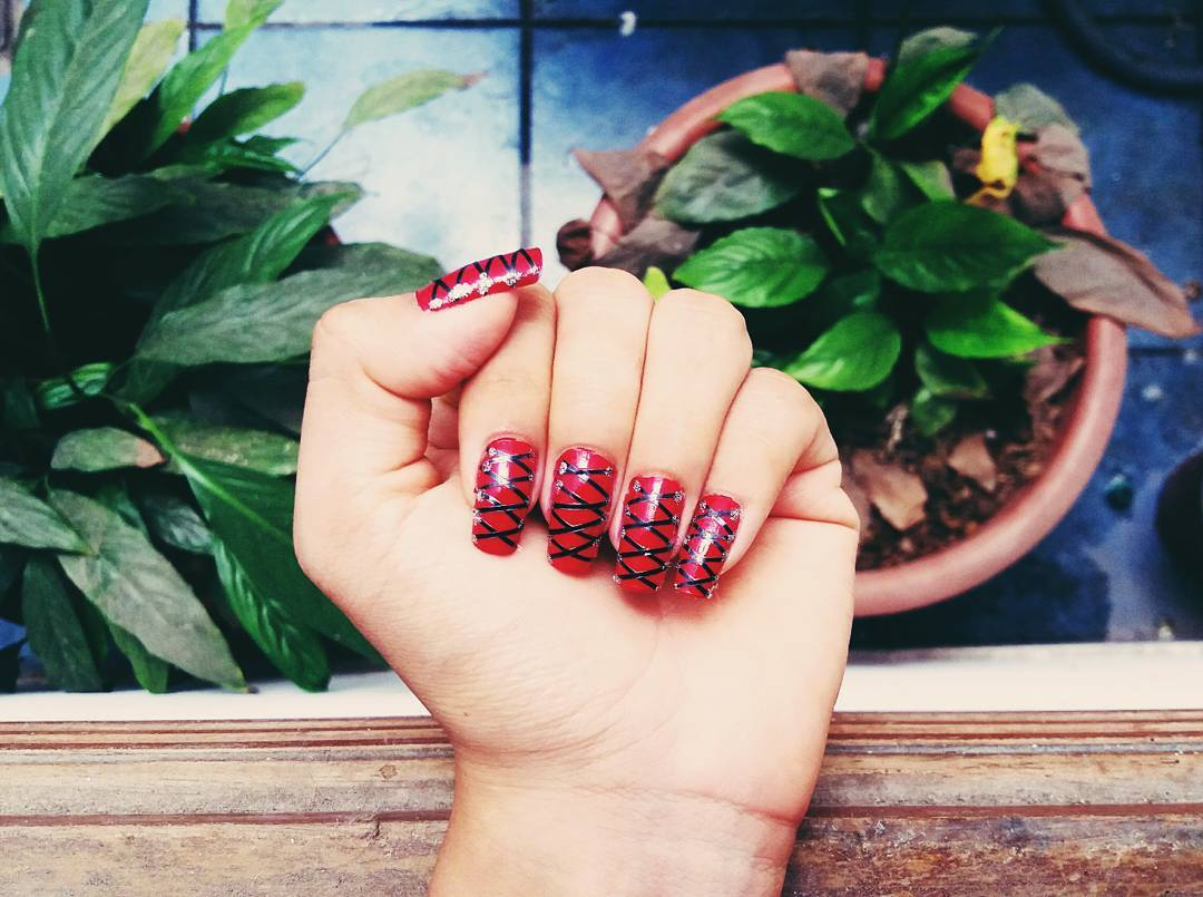 black lace design on red nails