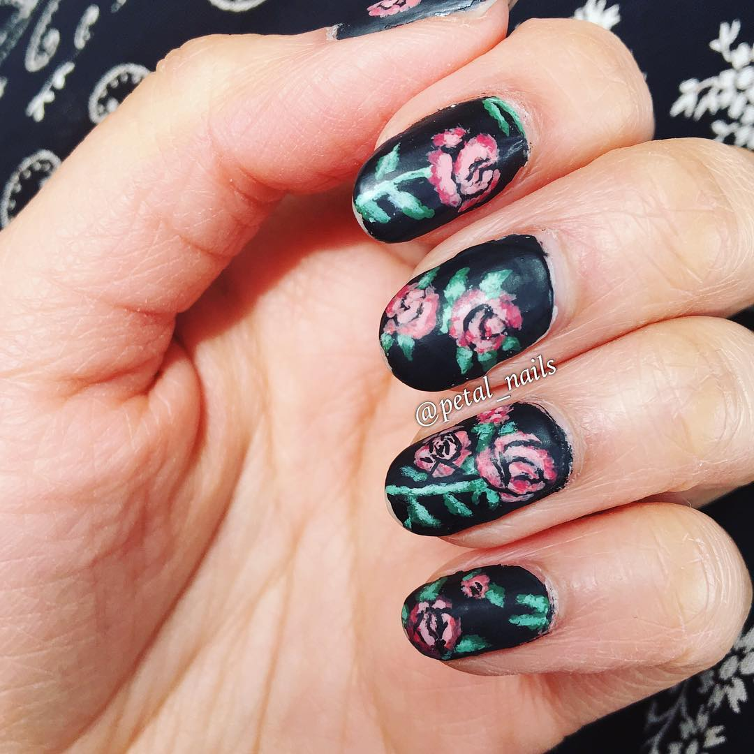 free hand rose design on black nails