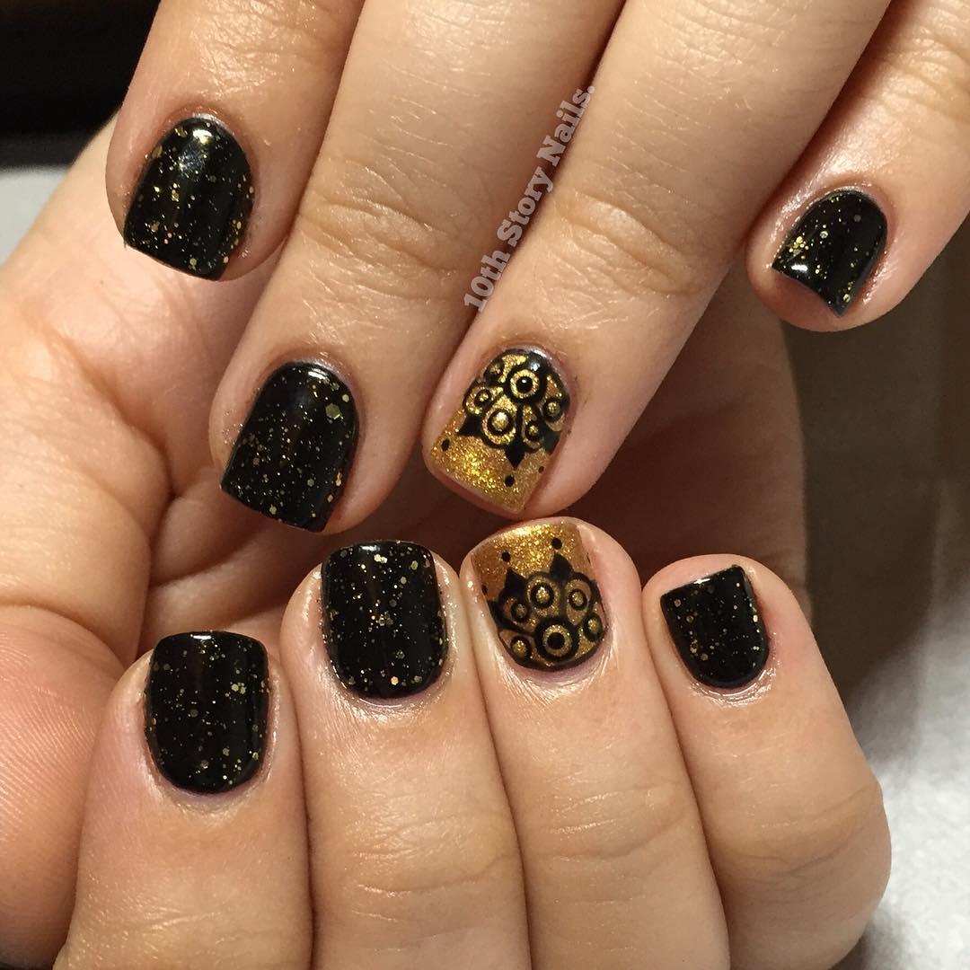 black and gold lace nail design