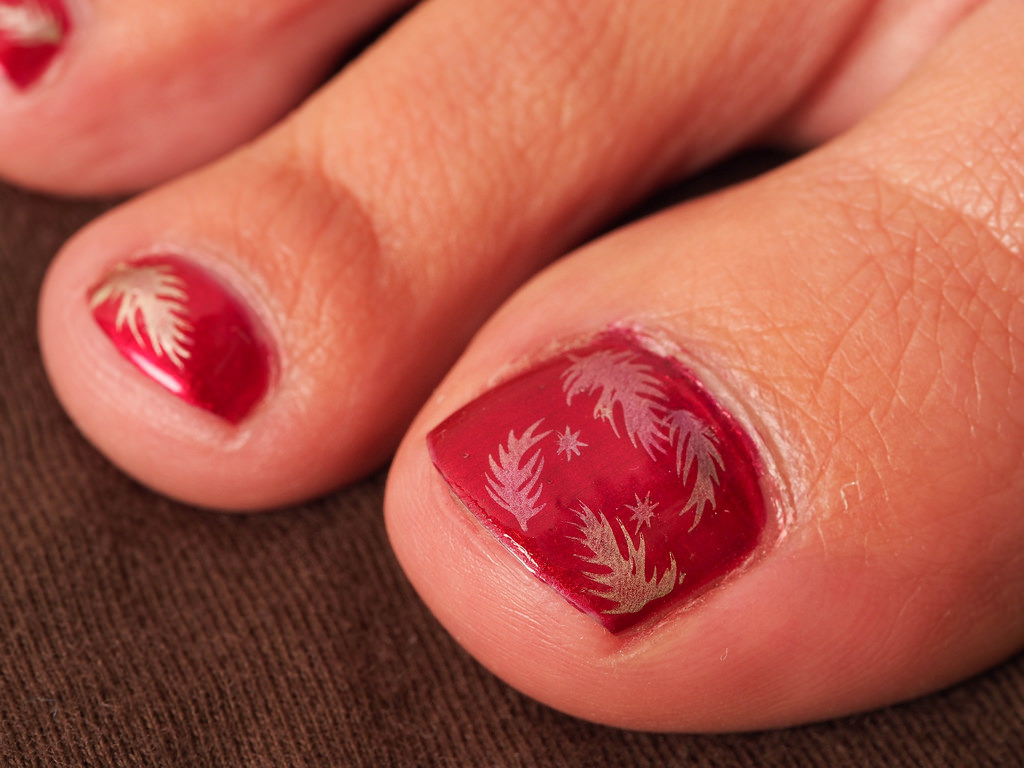 red colored fall design on toe nails
