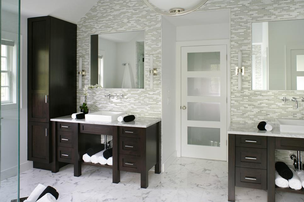 contemporary white bathroom features dark wood vanities