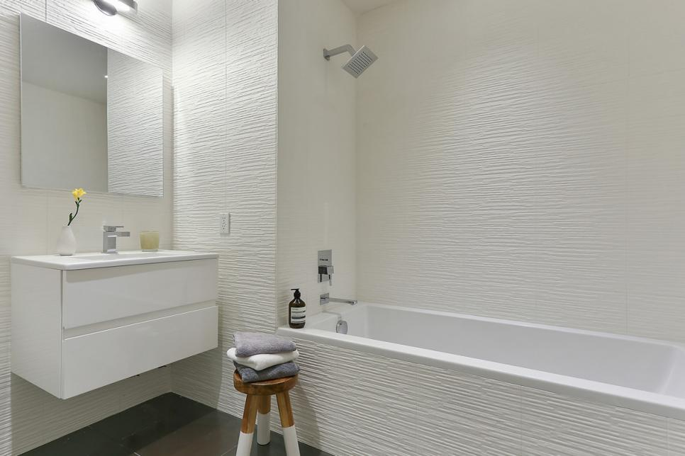 Crisp White Bathroom Boasts Floating Vanity & Textured Tile