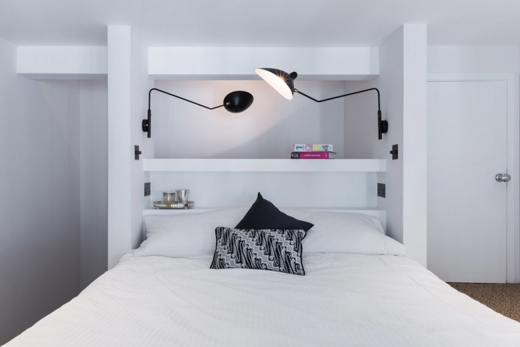 white bedroom design with black wall lamp
