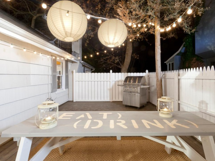 Patio With White Fence and String Lighting