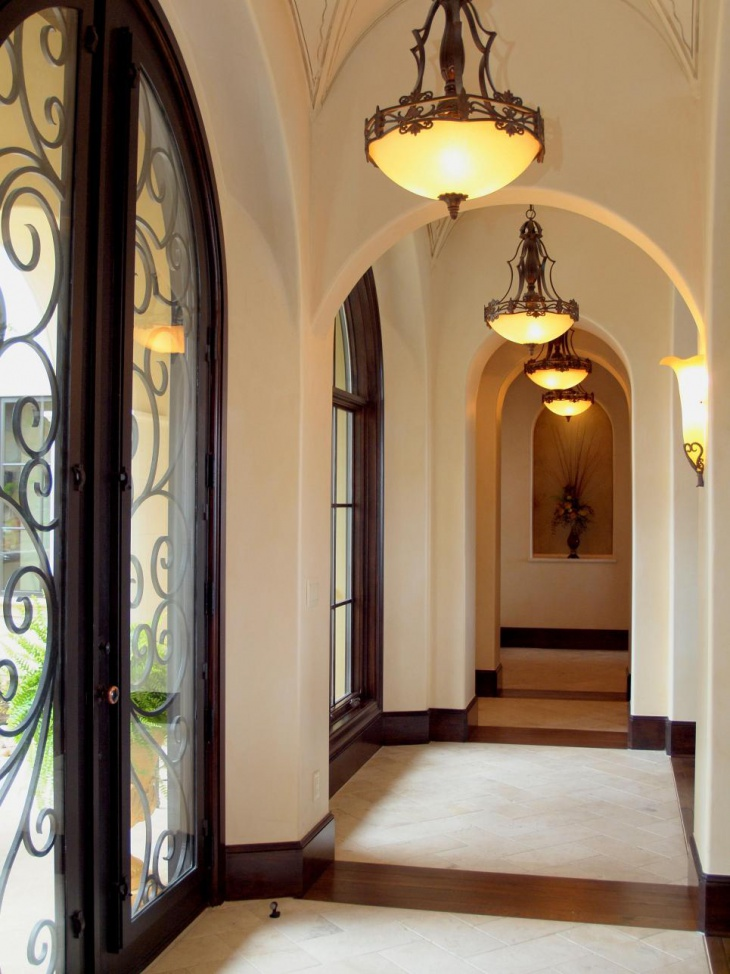 neutral archway hall with raditional light fixtures