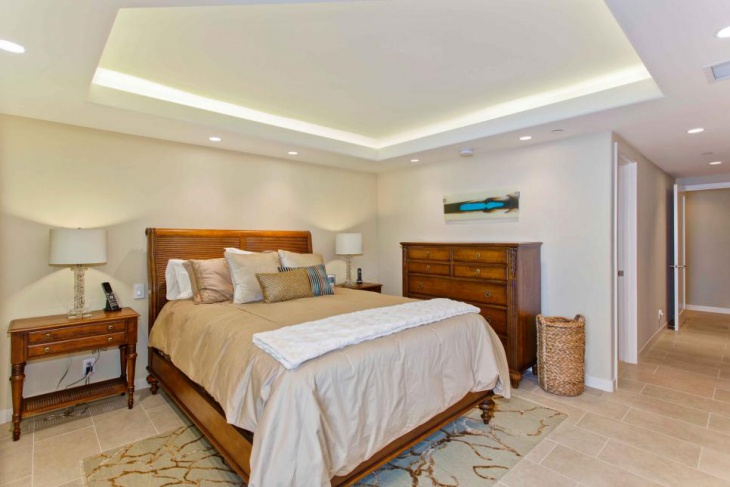 neutral bedroom boasts lighted tray ceiling