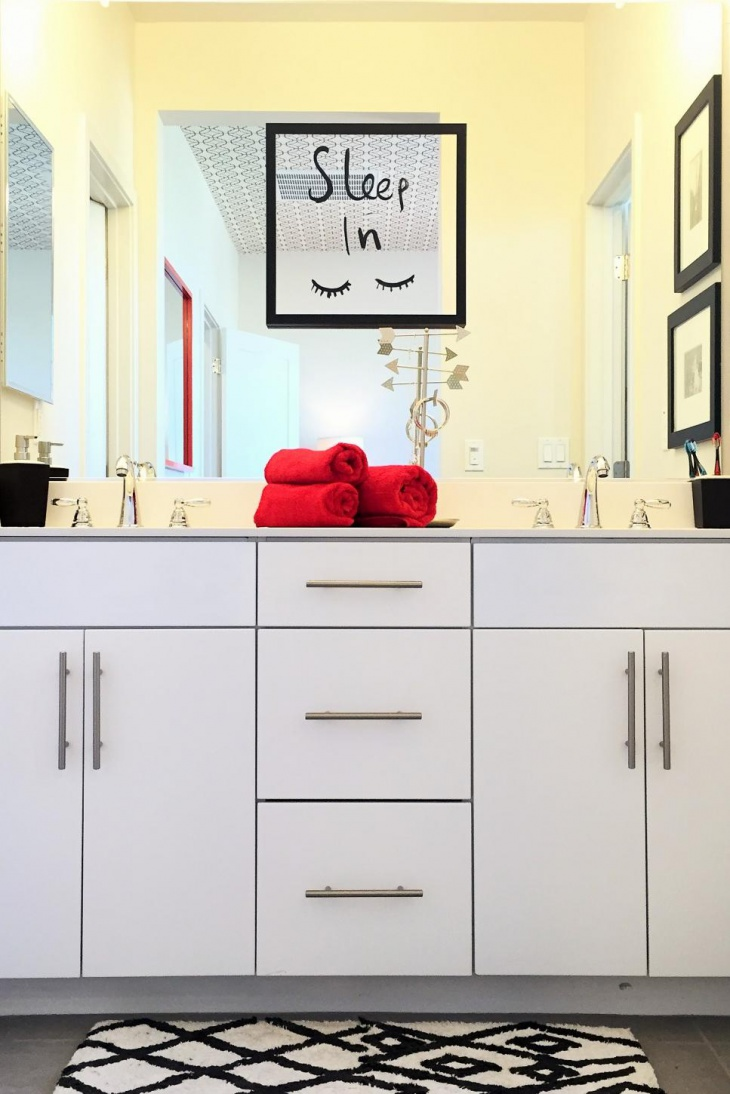 modern bathroom with cute mirror cling and red towels