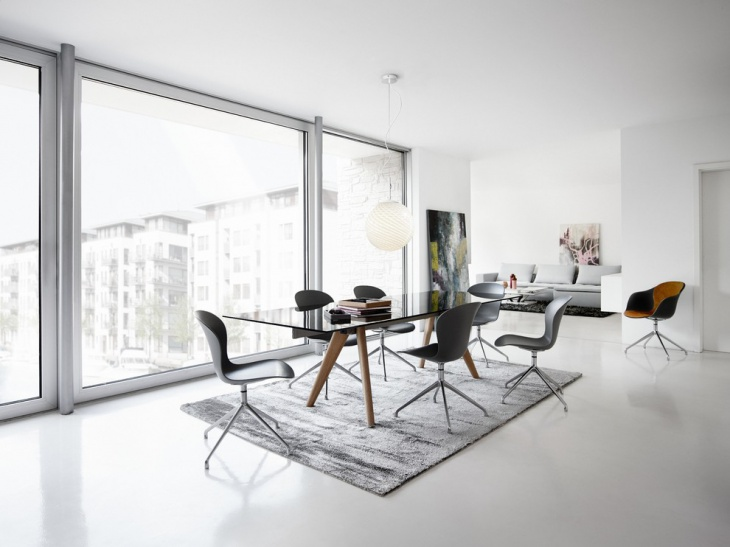black glass dining table with gray chairs