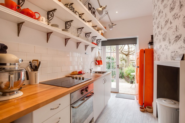 small narrow kitchen with orange accents