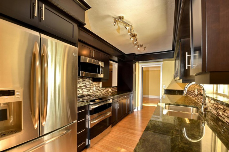 kitchen cabinets with golden granite countertops