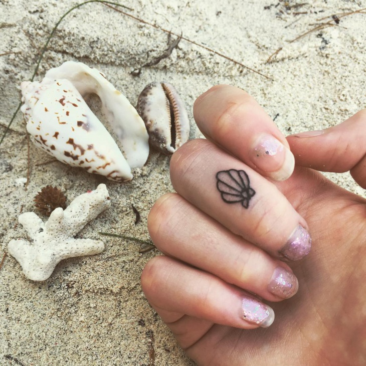 tiny shell tattoo on finger