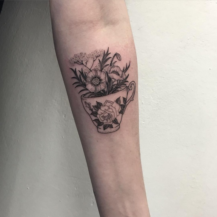 teacup tattoo on forearm