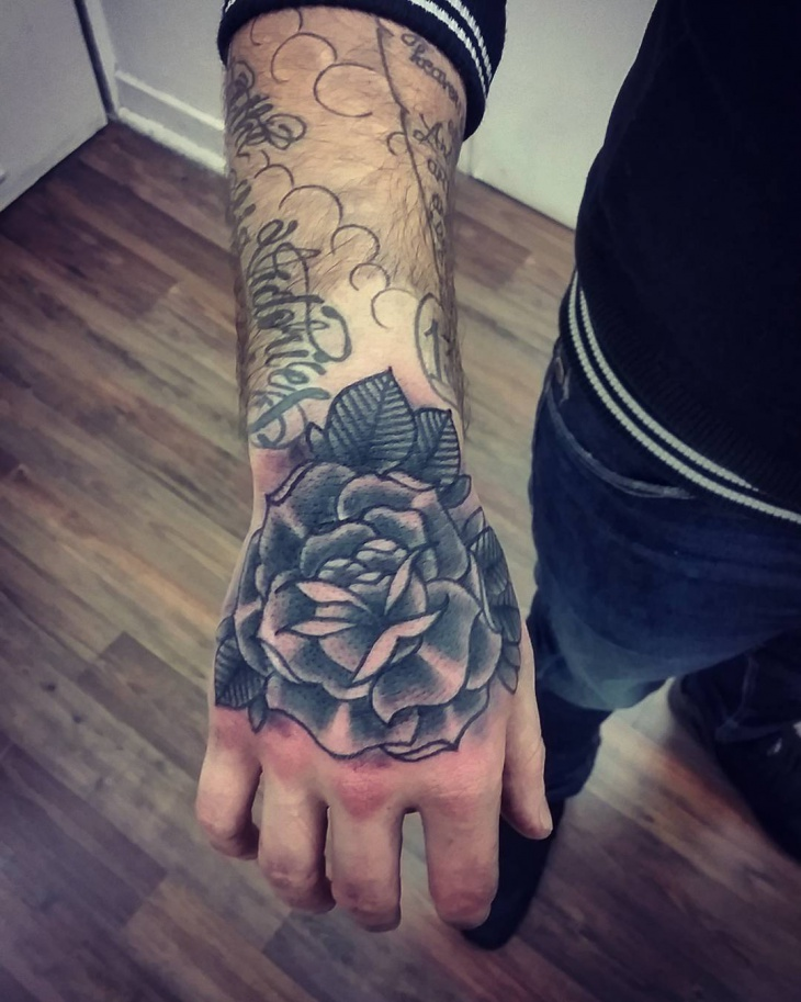 black flower tattoo on palm