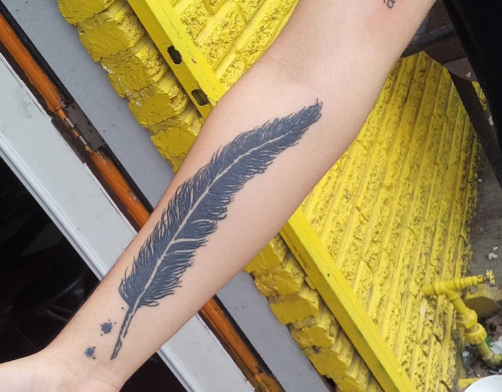 black feather tattoo on wrist
