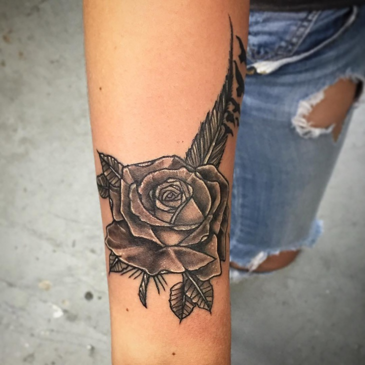 blackwork rose and feather tattoo