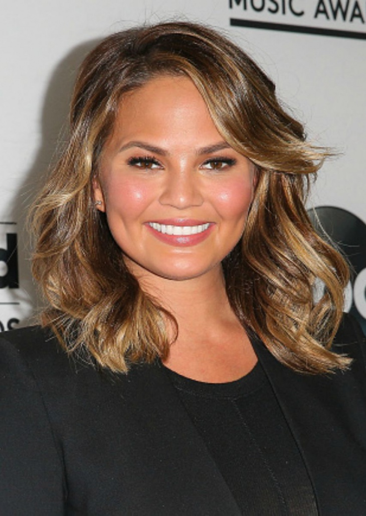 Chrissy Teigen Short Layered Curly Hairstyle For Round Faces