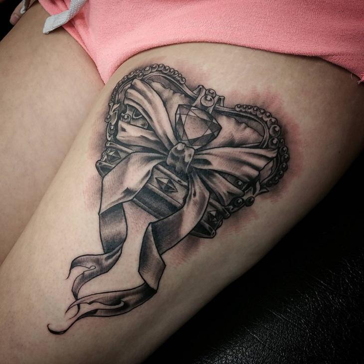 crown bow thigh tattoo