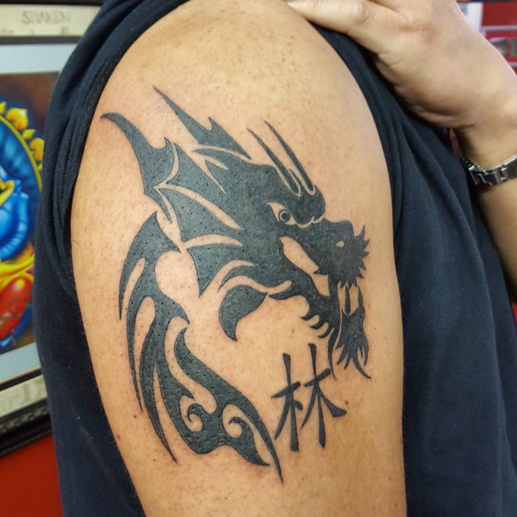tribal dragon tattoo on sleeve